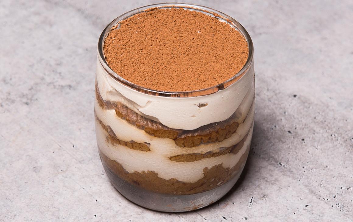 Clear glass of tiramisu, layered with cream and biscuits