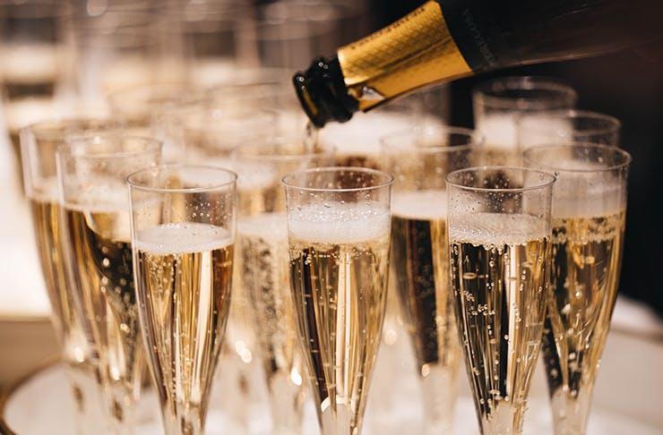 A champagne bottle filling up champagne glasses.