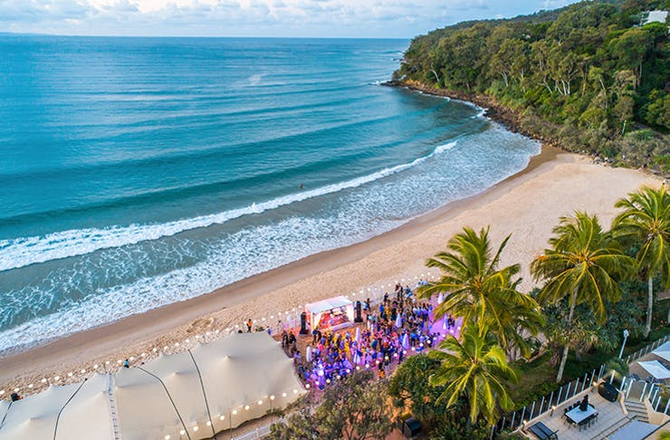 An aerial shot of a crowd on a beach under a white canopy of tents and fairy lights.