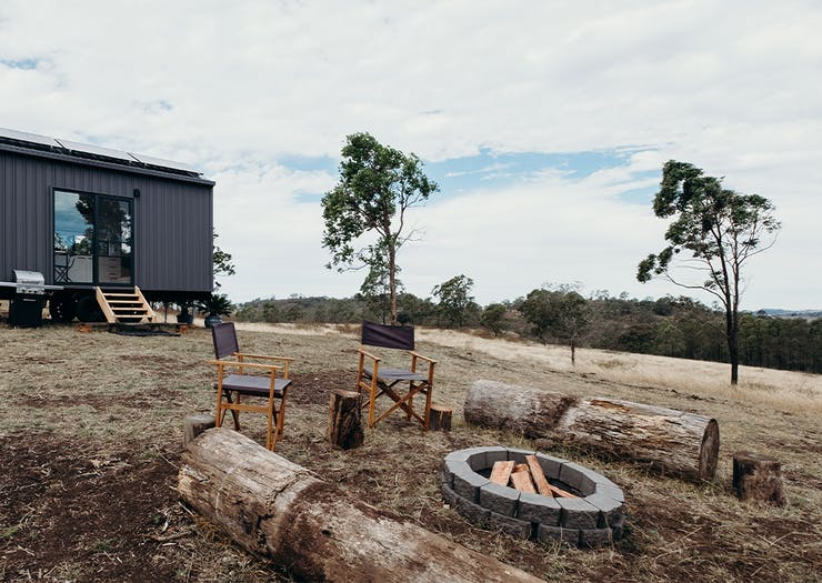 A cabin in a paddock with a campfire.