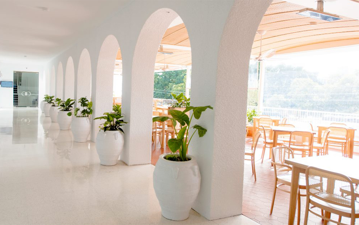 A white restaurant deck behind arched doorways