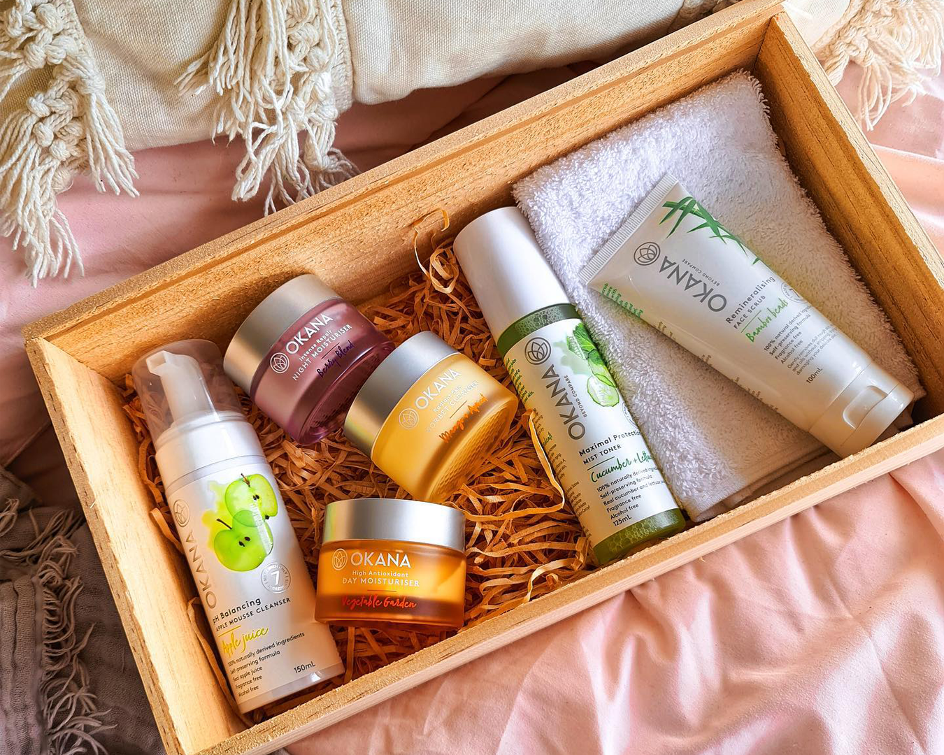 A wooden gift box containing bottles and pottles of pastel colours natural skincare