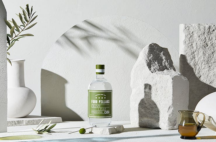 A bottle of Four Pillars Olive gin set on a concrete background and surrounded by olive leaves.