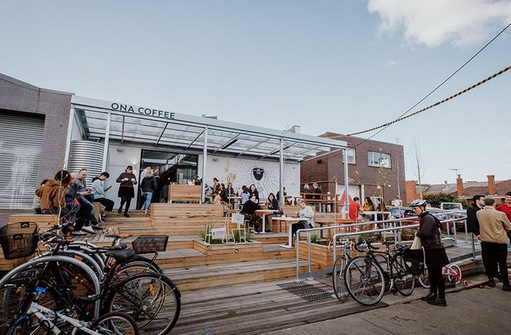A warehouse cafe drenched in sunlight. Cyclists sit out the front with parked bikes in bicycle lock-ups.