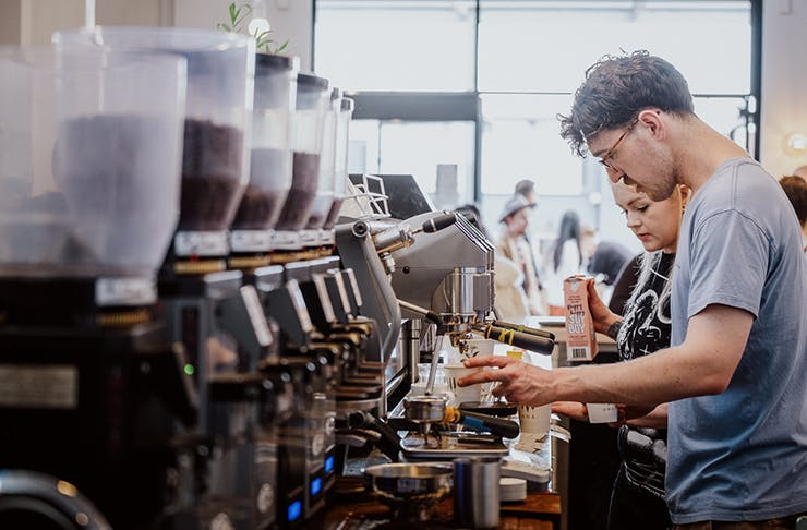 Two baristas making coffee by a long line of coffee machines.