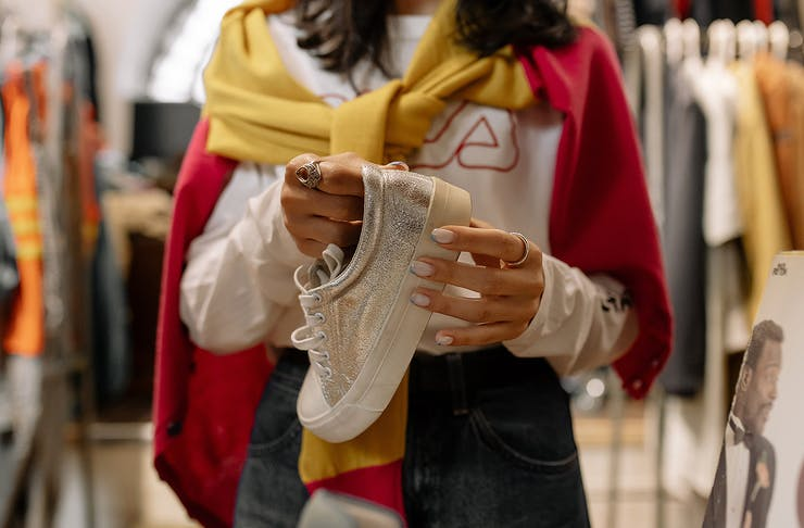 A person holds a sneaker to try on in a shop.