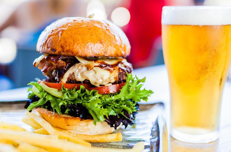 A deliciously-looking burger piled high with a meat patty, cheese, tomato and lettuce, sits alongside of a beer in a schooner glass.