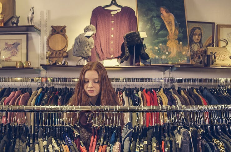 Girl rummaging through racks, best op and vintage shops in Christchurch