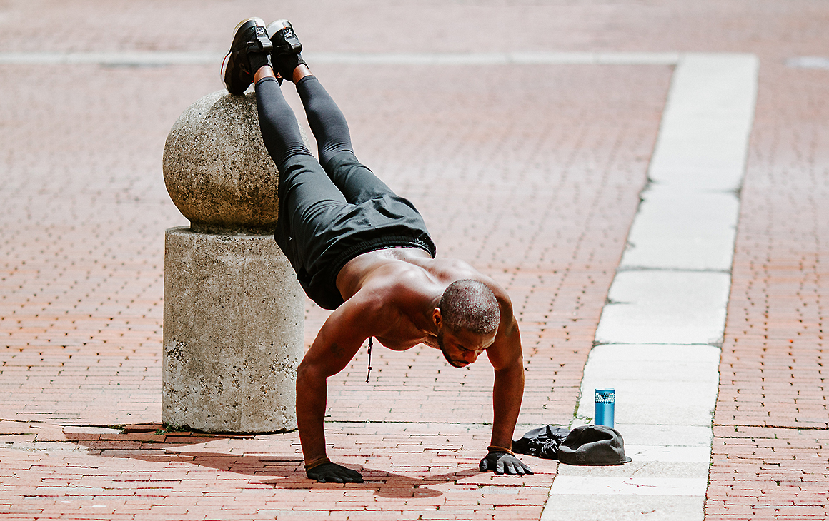 A man does push ups with his feet unfeasibly high on an outdoor sculpture. He looks very fit.