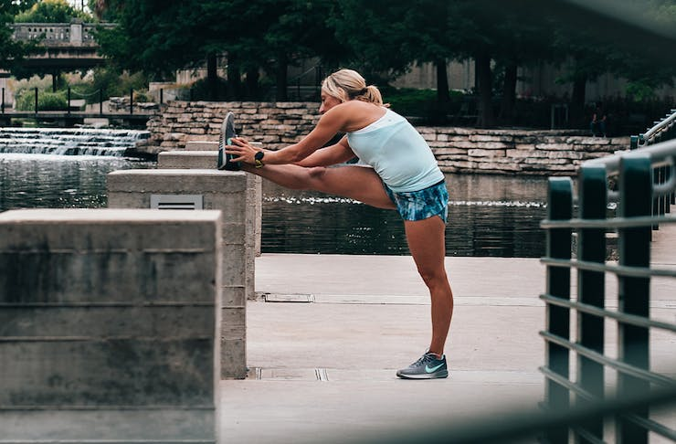 Woman in active wear with her foot up on a concrete barrier outdoors, stretching towards her foot.
