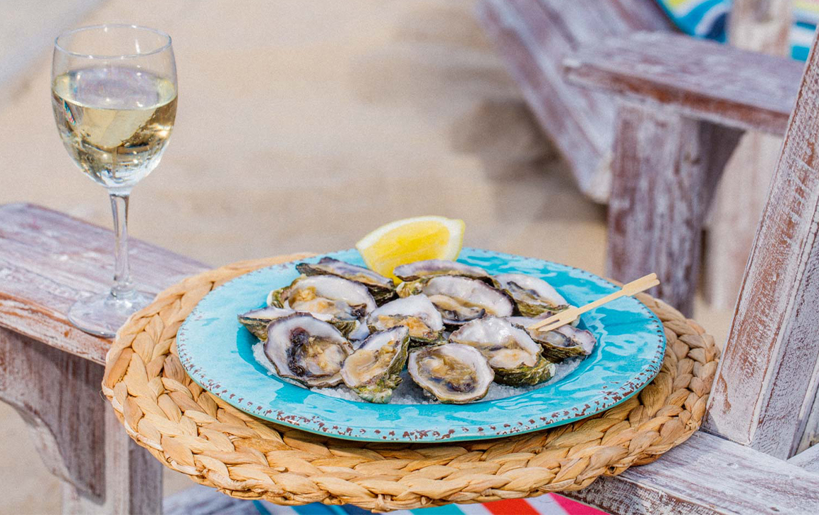 half a dozen oysters on a plate on the arm of a wooden chair with a glass of wine
