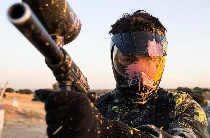 A man holding a paintball gun wearing a face shield