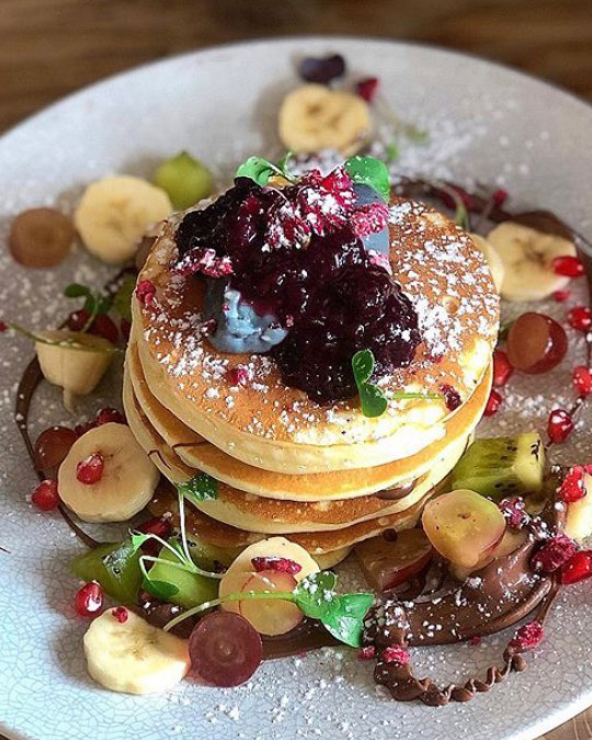 A stack of pancakes decorated with banana slices and blueberries