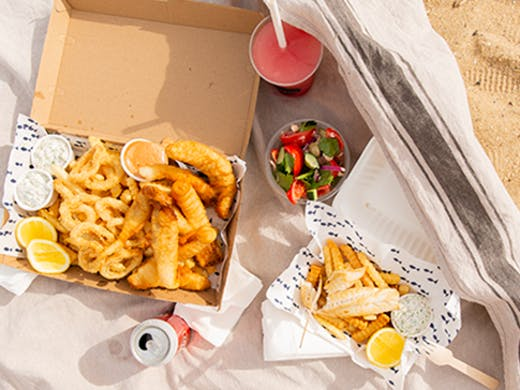 Fish and chips laid out on a towel on St Kilda Beach.