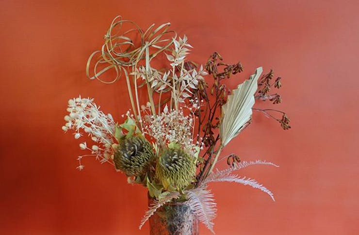 A dried flower arrangement in front of a red background.