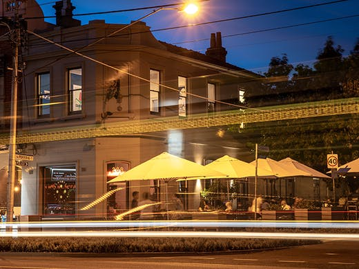 The exterior of Park Street Pasta & Wine with outdoor umbrellas and lights beaming.