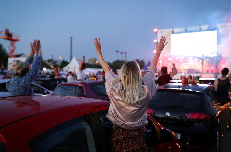 A woman with her hands raised, facing away from the camera towards a stage and a carpark full of cars and other people.