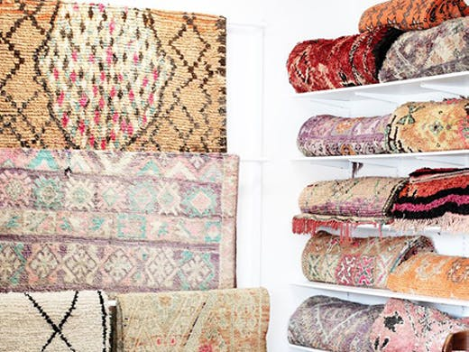 A beautiful collection of hanging and folded vintage Moroccan rugs.