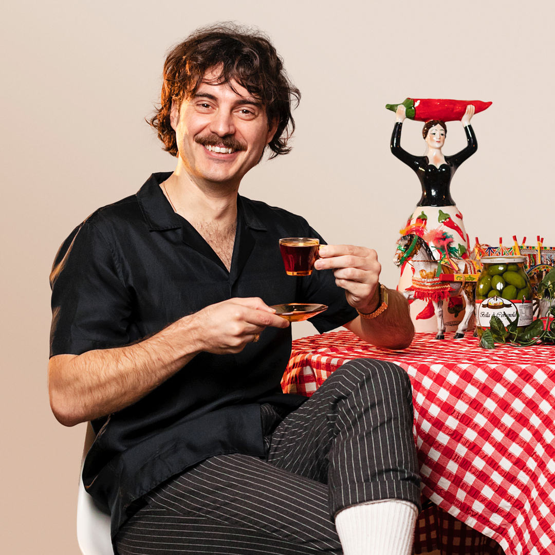 Andrew, the man behind Pasta Hotline, sits at a table sipping a coffee.