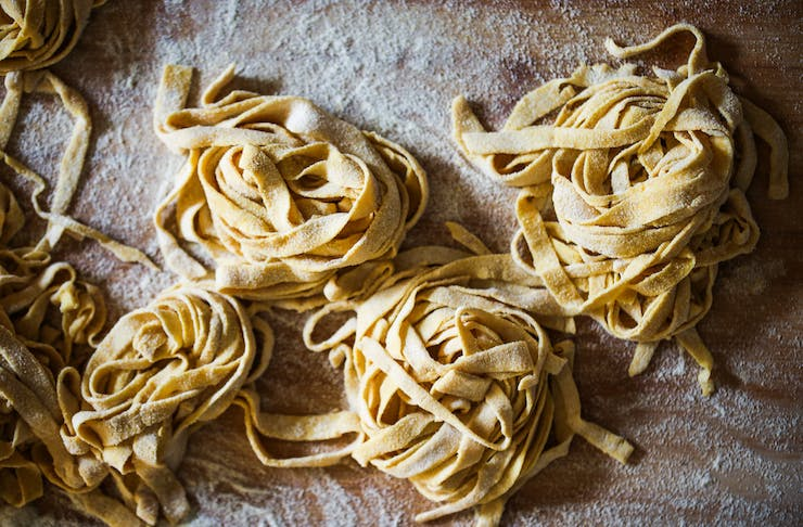 Fresh fettuccine pasta laid out in balls on a white surface.