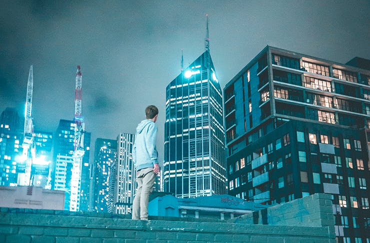 A man stands atop a wall looking at the Melbourne city skyline at night.
