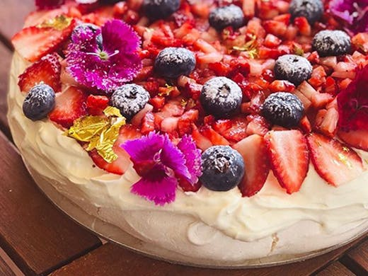 A fresh-made pavlova covered in berries.
