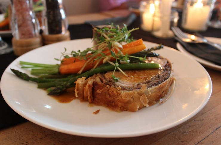 Colourful main dish of pork wrapped in flaky bread crust topped with asparagus, carrots and microgreens