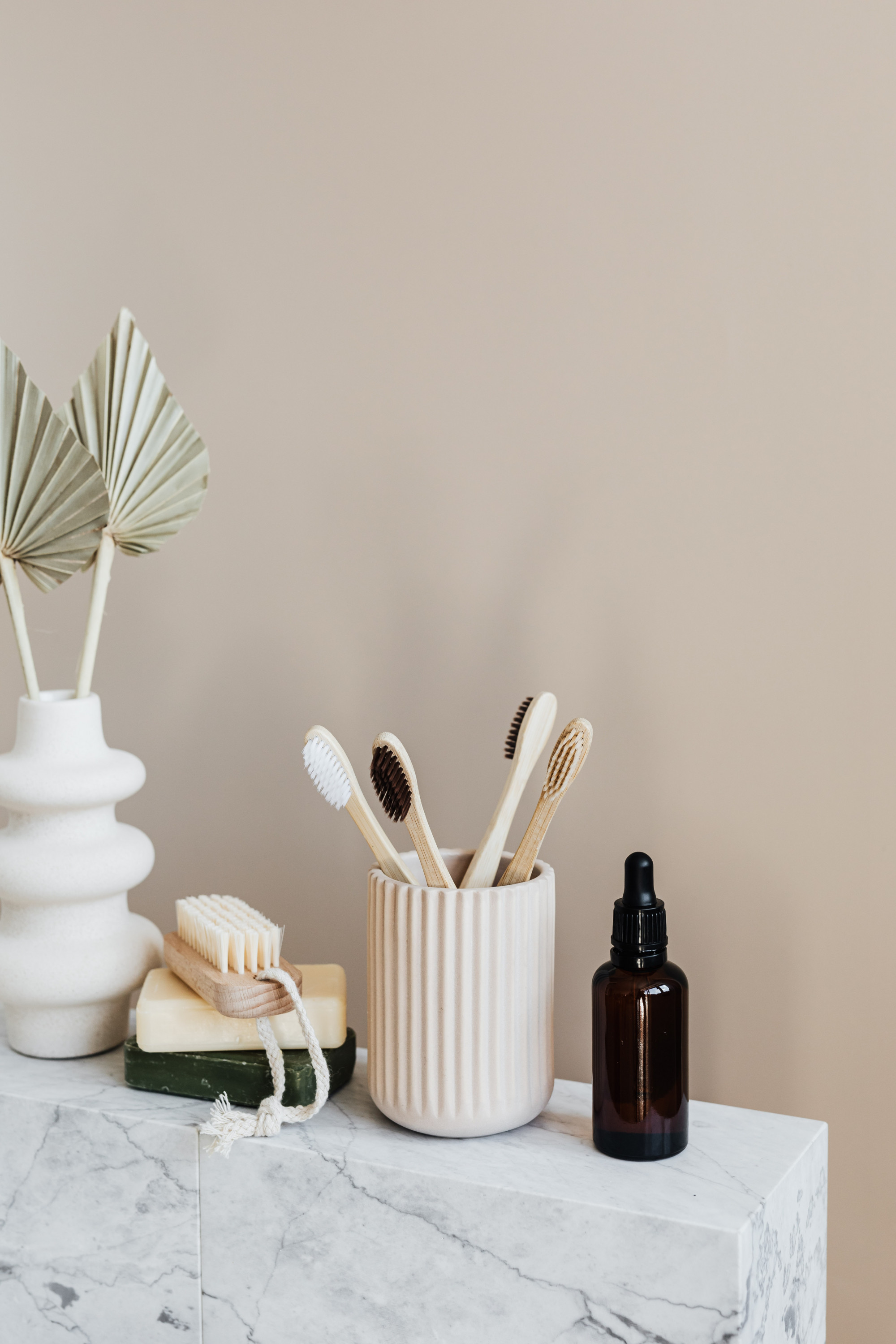 A shot of four bamboo toothbrushes in a ceramic holder, alongside a serum bottle and a nail brush.