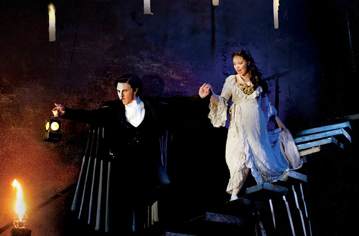 The Phantom of the Opera walking down a stone staircase holding a woman's hand.