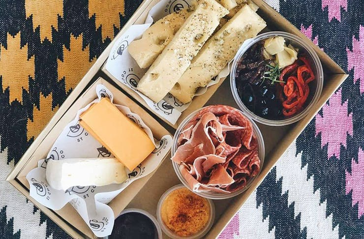 A cardboard box filled with cheese on a picnic rug