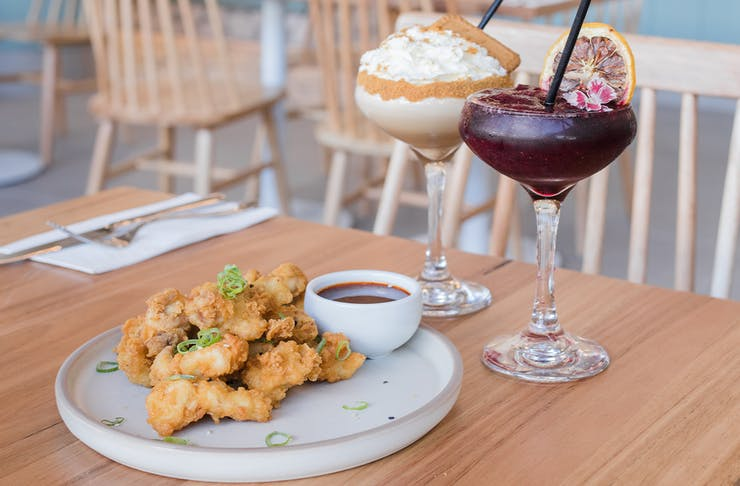 a plate of karaage chicken and two cocktails