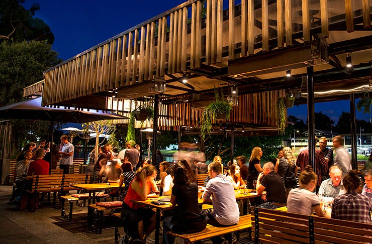 A bar lit up at night time by the Yarra River.