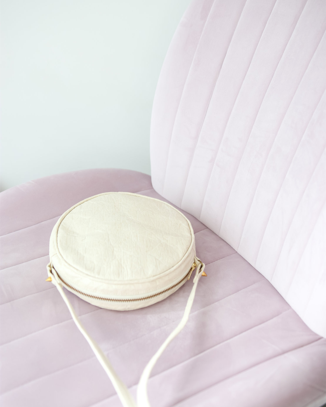 A lilac velvet chair with a white circular handbag lying on it