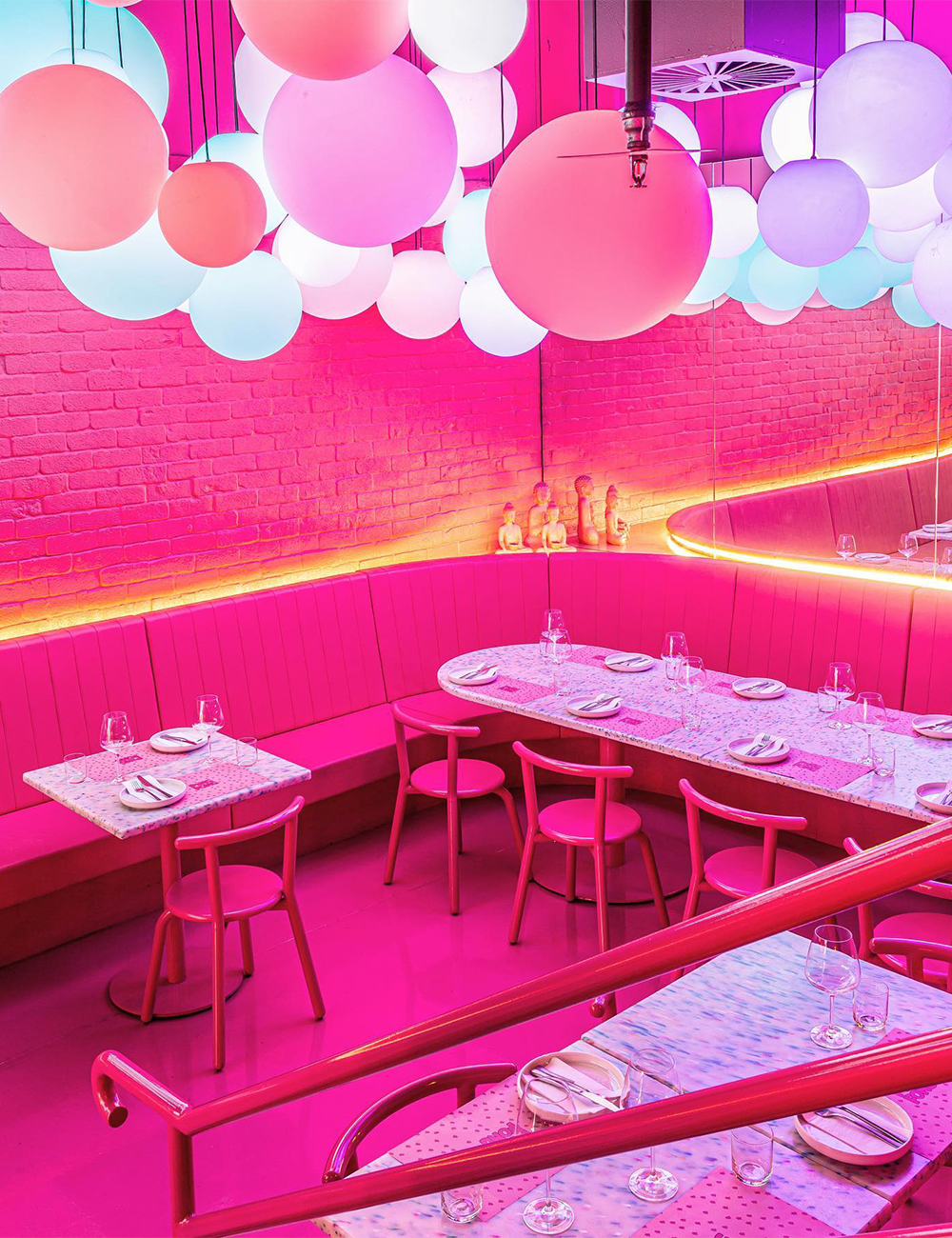 Hot Pink sitting area in restaurant with lots of pastel balls hanging from the ceiling