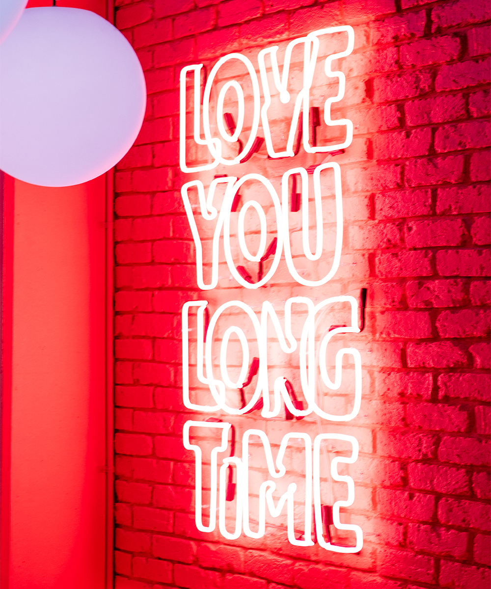 a neon sign saying 'love you long time'