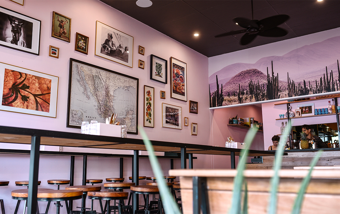 a pink restaurant interior with framed images on the walls