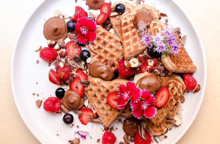 a plate of heart shaped mini waffles topped with raspberries and chocolate mousse