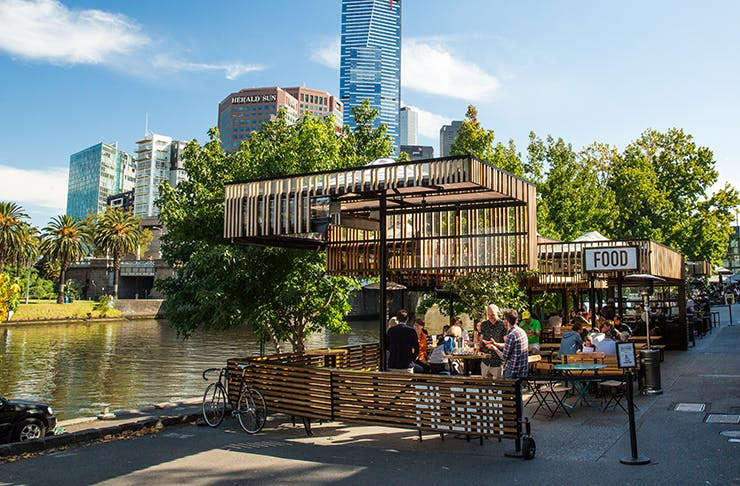 An open air bar by the river drenched in sunlight.