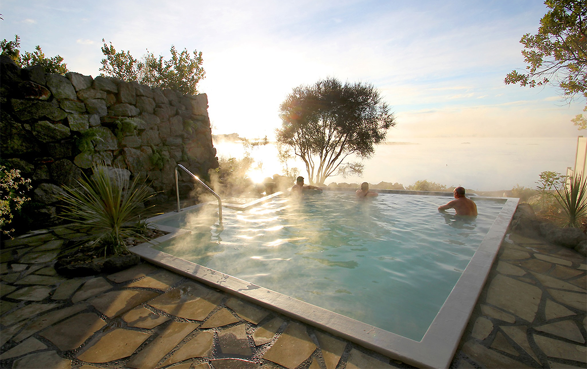 The Polynesian Spa in Rotorua, one of the best natural hot pools in New Zealand. This image shows a pool surrounded by rocks.