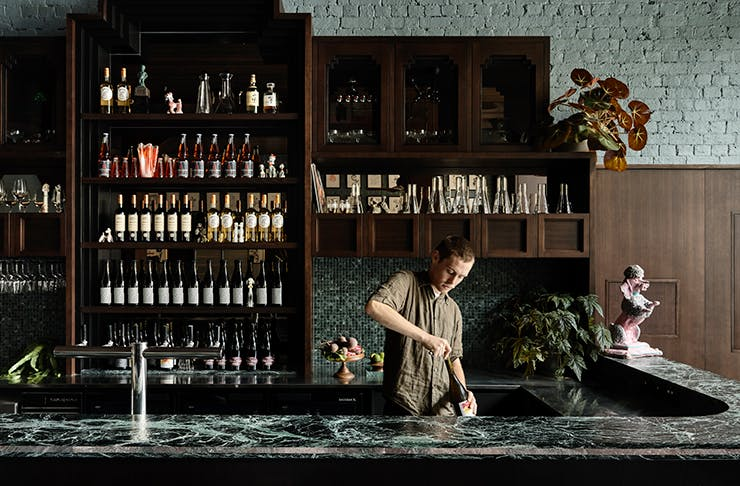 A man serving a cocktail on a granite bar.