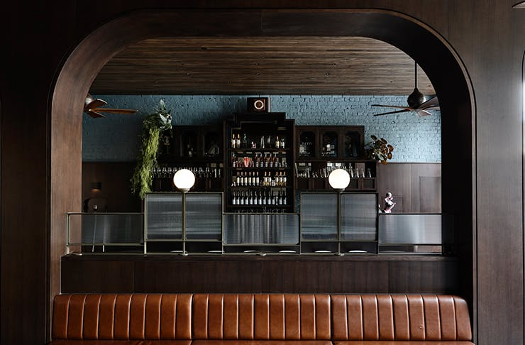 An art-deco style bar with dim lights and a full bar.