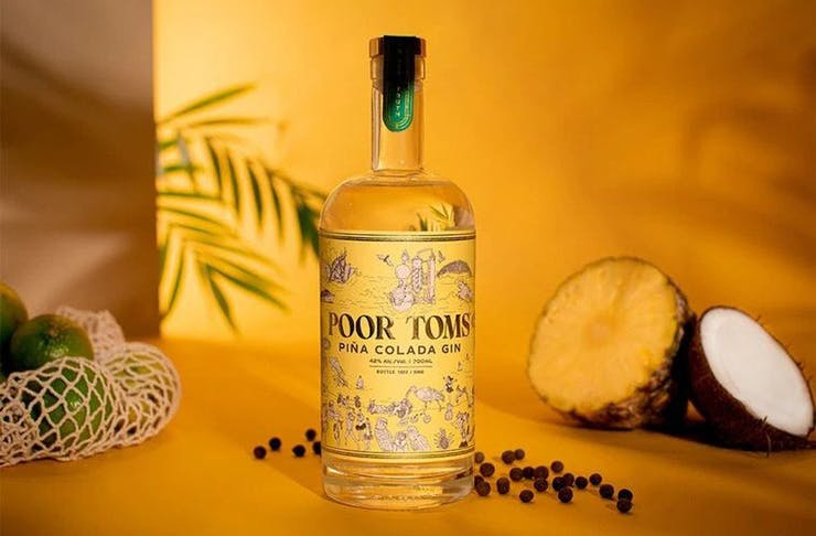 Poor Toms piña colada gin on a surface surrounded by coconut, pineapple, and palm leaves.