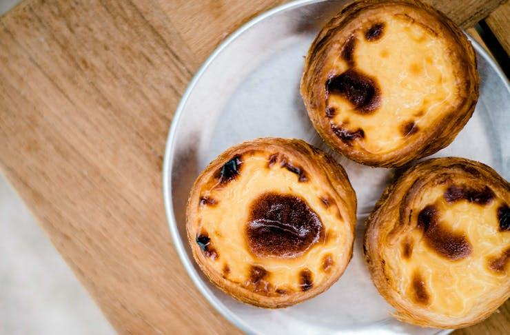 three portuguese tarts on a plate