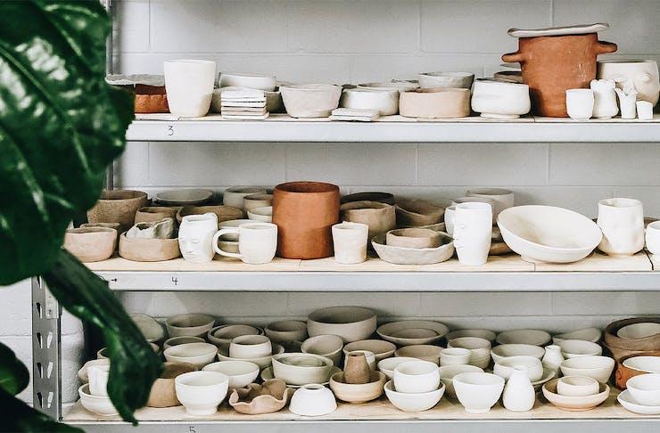 shelves full of drying pottery