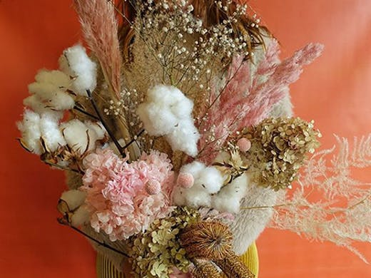 A stunning dried flower arrangement in front of a multicoloured background.