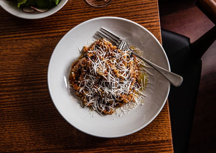 A bowl of pasta with grated cheese