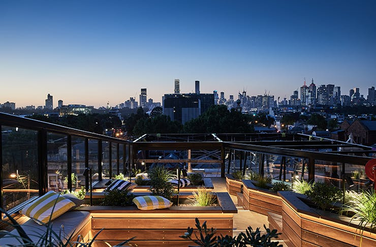 A fancy rooftop bar overlooking the Melbourne skyline at night.