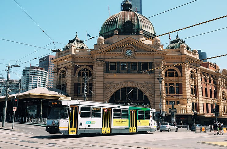 A tram passing by Flinders Street Station on a sunny day.