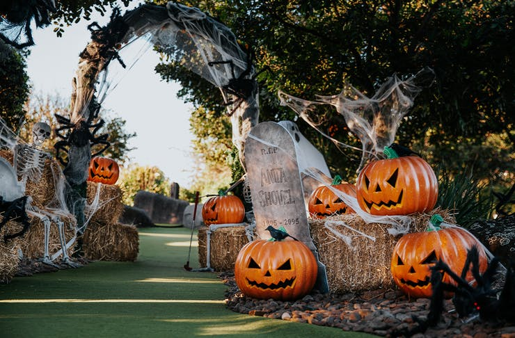 a mini golf course covered in pumpkins and cobwebs