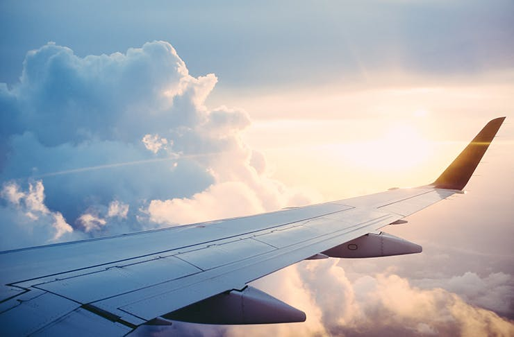 A view from a window seat in a plane looking out toward a cloudy sky.